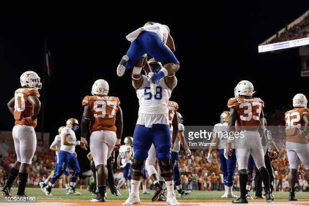 Willie Wright of the Tulsa Golden Hurricane lifts Shamari Brooks after a rushing touchdown in the second half against the Texas Longhorns at Darrell...