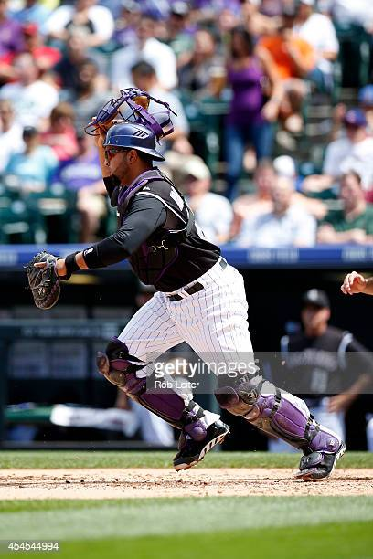 Willin Rosario of the Colorado Rockies catches during the game against the Chicago Cubs at Coors Field on August 7 2014 in Denver Colorado The Cubs...