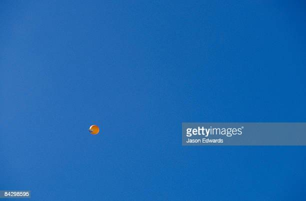 A bright orange weather balloon flying against a clear blue sky.