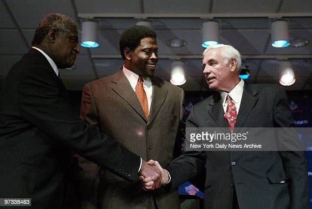 Willis Reed shakes hands with Dave DeBusschere as Patrick Ewing looks on during a news conference at the Theater in Madison Square Garden before...