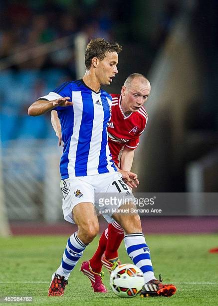 Willo Flood of Aberdeen duels for the ball with Sergio Canales of Real Sociedad during the UEFA Europa League third round qualifying first leg match...