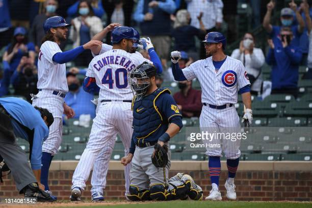 Willson Contreras and teammates of the Chicago Cubs celebrate in front of Manny Pina of the Milwaukee Brewers after his three run home run in the...