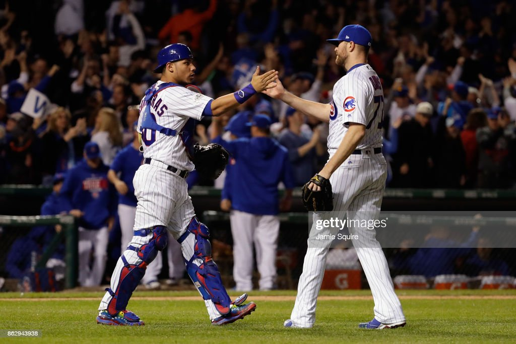 Willson Contreras #40 and Wade Davis #71 of the Chicago Cubs celebrate after beating the Los Angeles Dodgers 3-2 in game four of the National League Championship Series at Wrigley Field on October 18, 2017 in Chicago, Illinois.