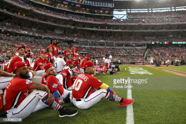 Willson Contreras of the Chicago Cubs and the National League looks on with teammates as Rhys Hoskins of the Philadelphia Phillies and National...