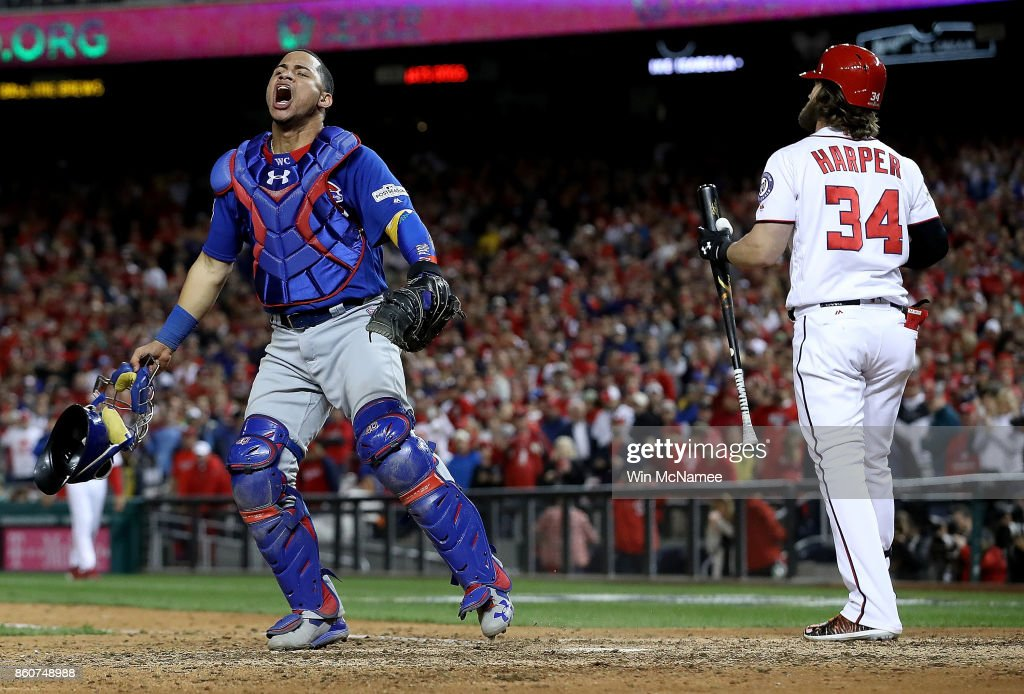 Willson Contreras #40 of the Chicago Cubs celebrates next to Bryce Harper #34 of the Washington Nationals after Harper struck out to end Game 5 of the National League Divisional Series at Nationals Park on October 13, 2017 in Washington, DC. The Cubs won the game 9-8 and will advance to the National League Championship Series against the Los Angeles Dodgers.
