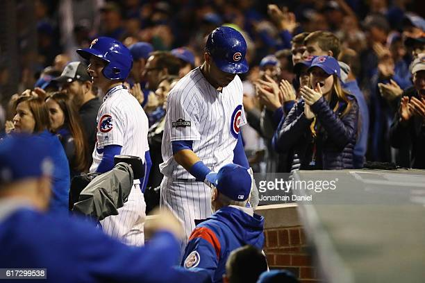 Willson Contreras of the Chicago Cubs celebrates with manager Joe Maddon at the dugout after hitting a solo home run in the fourth inning against the...