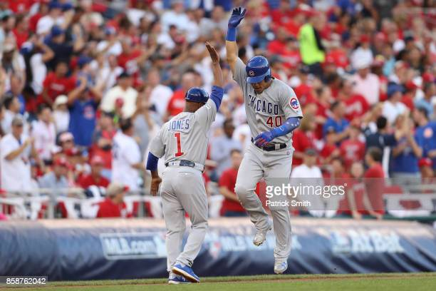 Willson Contreras of the Chicago Cubs celebrates with third base coach Gary Jones of the Chicago Cubs after hitting a solo home run against the...