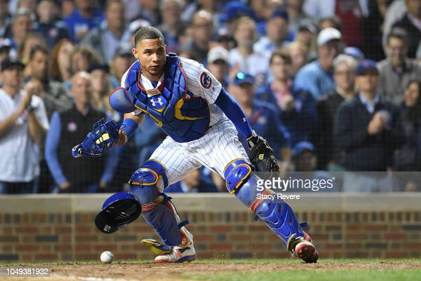 Willson Contreras of the Chicago Cubs checks a runer after a wild pitch during the National League Wild Card game against the Colorado Rockies at...