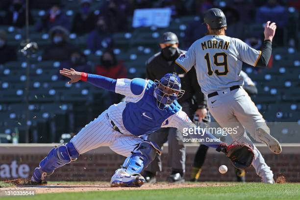 Willson Contreras of the Chicago Cubs dives for a relay throw as Colin Moran of the Pittsburgh Pirates runs past to score a run in the fifth inning...