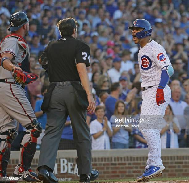 Willson Contreras of the Chicago Cubs has words with Tyler Flowers of the Atlanta Braves and home plate umpire John Tumpane after hitting a solo home...