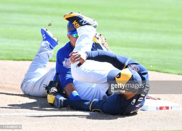 Willson Contreras of the Chicago Cubs is tagged out at third base by Tyler Saladino of the Milwaukee Brewers during the first inning of a spring...