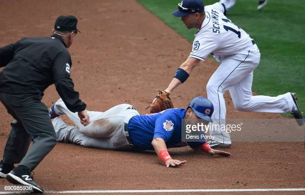Willson Contreras of the Chicago Cubs is tagged out by Ryan Schimpf of the San Diego Padres as he tries to steal third base during the second inning...