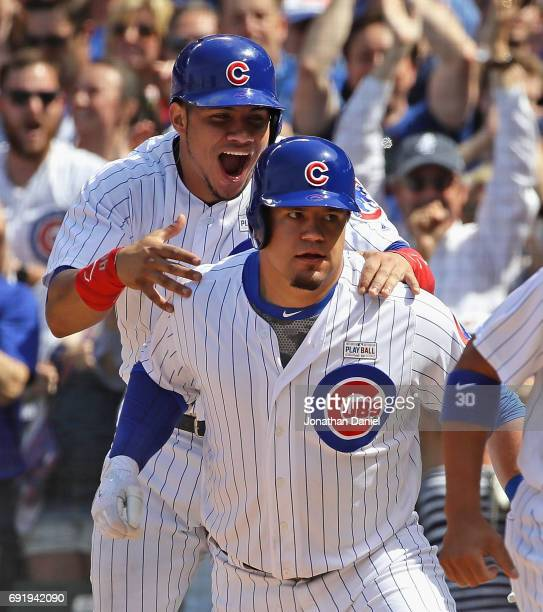 Willson Contreras of the Chicago Cubs jumps on the back of teammate Kyle Schwarber after Schwarber hit a grand slam home run in the 7th inning...