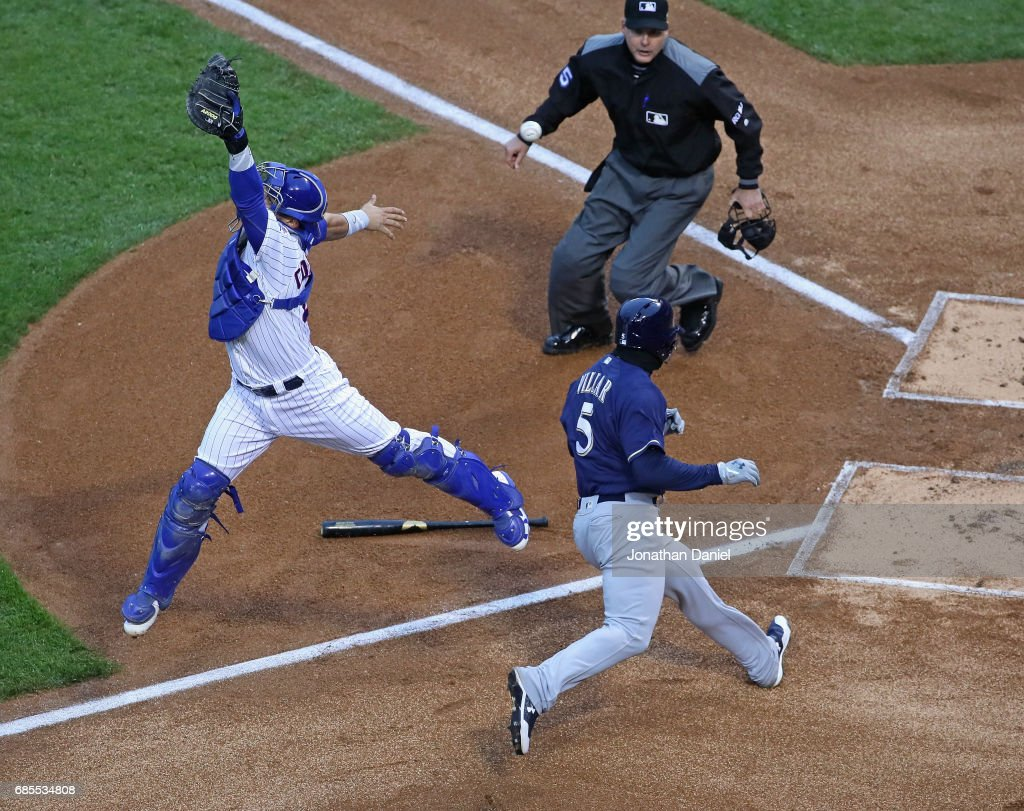 Willson Contreras #40 of the Chicago Cubs leaps in vain to try to catch a relay throw as Jonathan Villar #5 of the Milwaukee Brewers moves in score a run in the 6th inning at Wrigley Field on May 19, 2017 in Chicago, Illinois. The Brewers defeated the Cubs 6-3.