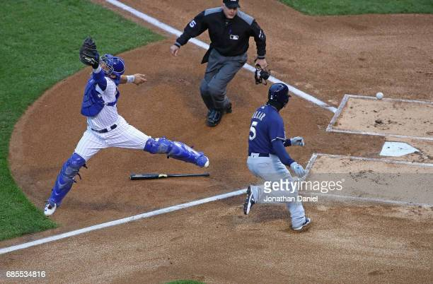 Willson Contreras of the Chicago Cubs leaps in vain to try to catch a relay throw as Jonathan Villar of the Milwaukee Brewers moves in score a run in...
