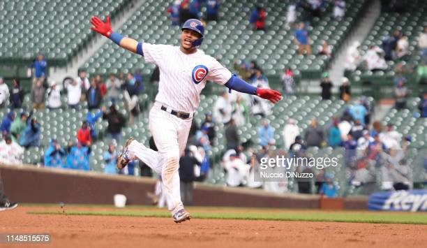 Willson Contreras of the Chicago Cubs rounds the base following his 15th inning walkoff home run against the Milwaukee Brewers at Wrigley Field on...
