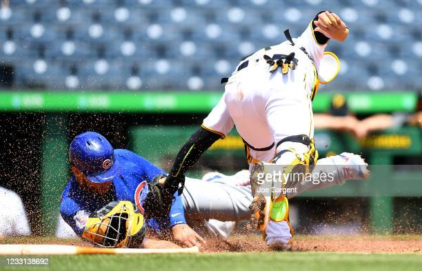 Willson Contreras of the Chicago Cubs scores past Michael Perez of the Pittsburgh Pirates during the third inning at PNC Park on May 27, 2021 in...