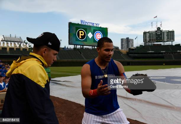 Willson Contreras of the Chicago Cubs shows Jose Lopez a catcher stance before a game between the Chicago Cubs and the Pittsburgh Pirates on August...