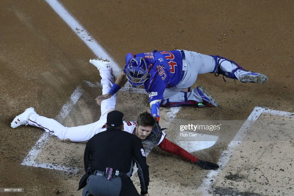 Willson Contreras #40 of the Chicago Cubs tags out Trea Turner #7 of the Washington Nationals at the plate during the first inning in game five of the National League Division Series at Nationals Park on October 12, 2017 in Washington, DC.