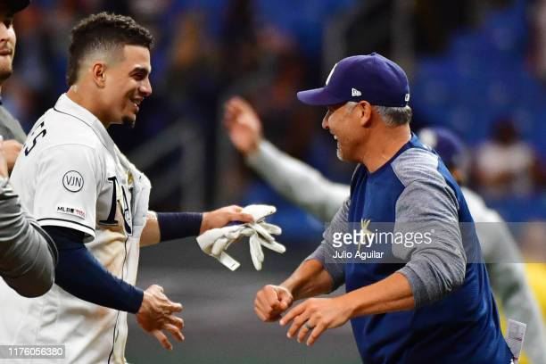 Willy Adames and Kevin Cash of the Tampa Bay Rays celebrate after an eleventh inning 54 win over the Boston Red Sox at Tropicana Field on September...