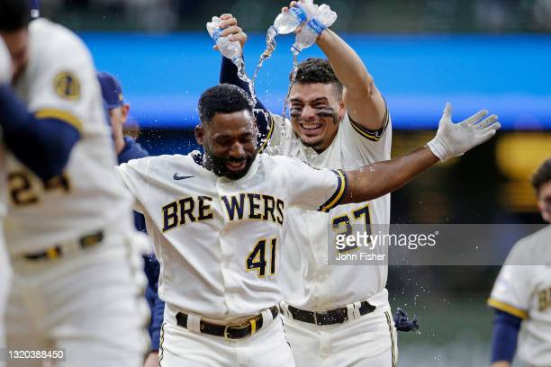 Willy Adames of the Milwaukee Brewers congratulates Jackie Bradley Jr. #41 of the Milwaukee Brewers on the game winning hit in the tenth inning...