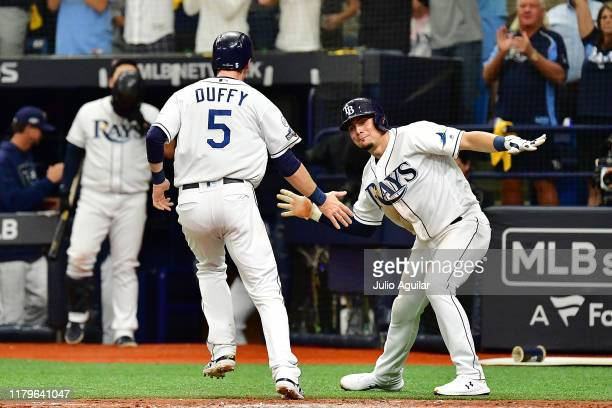 Willy Adames of the Tampa Bay Rays celebrates with Matt Duffy after scoring a run against the Houston Astros during the fourth inning in Game Three...