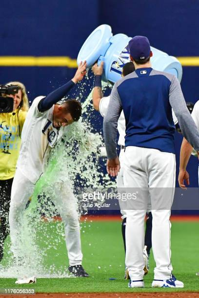 Willy Adames of the Tampa Bay Rays gets a cooler dumped by Tommy Pham after hitting an RBI walkoff in the eleventh inning off of Trevor Kelley of the...