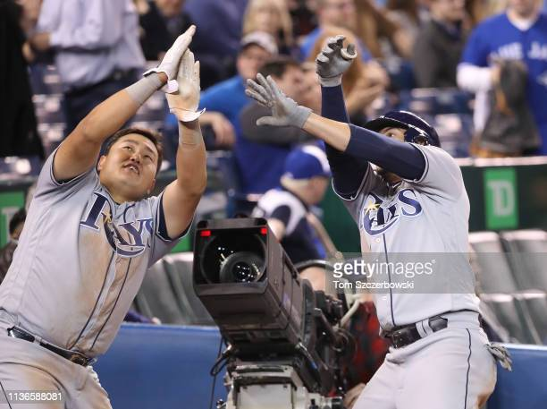 Willy Adames of the Tampa Bay Rays is congratulated by JiMan Choi after hitting a tworun home run in the ninth inning during MLB game action against...
