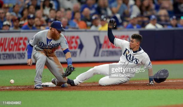 Willy Adames of the Tampa Bay Rays slides in safely to third base as Justin Turner of the Los Angeles Dodgers cannot field the throw in the seventh...