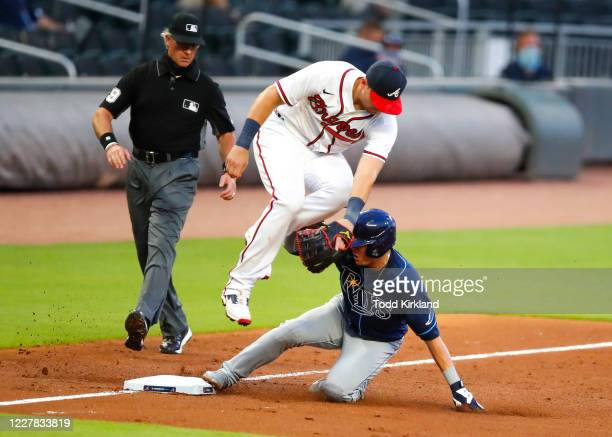 Willy Adames of the Tampa Bay Rays slides under Austin Riley of the Atlanta Braves and rounds third to score on a throwing error in the fifth inning...