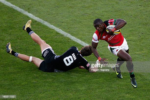 Willy Ambaka of Kenya beats the tackle of Gillies Kaka of New Zealand in the semifinal cup match between New Zealand and Kenya during the 2013...
