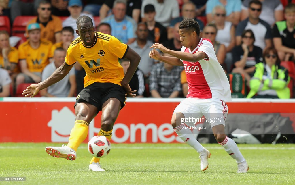 Willy Boly of Wolverhampton passes the ball as David Neres challenges during the pre seaon friendly match between Wolverhampton Wanderers and Ajax at the Banks' Stadium on July 19, 2018 in Walsall, England.