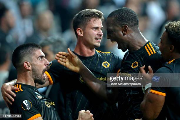 Willy Boly of Wolverhampton Wanderers celebrates with teammates Ruben Neves and Leander Dendoncker after scoring his team's first goal during the...