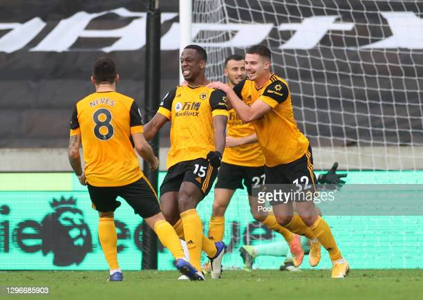 Willy Boly of Wolverhampton Wanderers celebrates with teammates Ruben Neves and Leander Dendoncker after scoring his team's second goal during the...