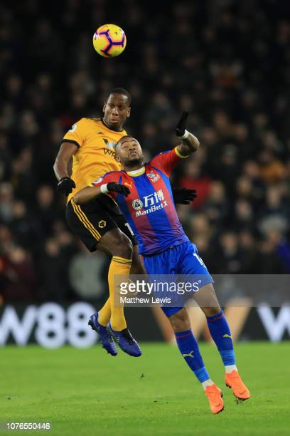 Willy Boly of Wolverhampton Wanderers competes for a header with Jordan Ayew of Crystal Palace during the Premier League match between Wolverhampton...