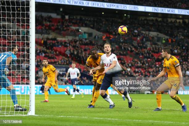 Willy Boly of Wolves pulls on the shirt of Harry Kane of Tottenham during the Premier League match between Tottenham Hotspur and Wolverhampton...
