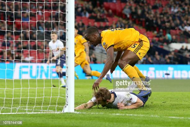 Willy Boly of Wolves steps on Harry Kane of Tottenham after bringing him down during the Premier League match between Tottenham Hotspur and...