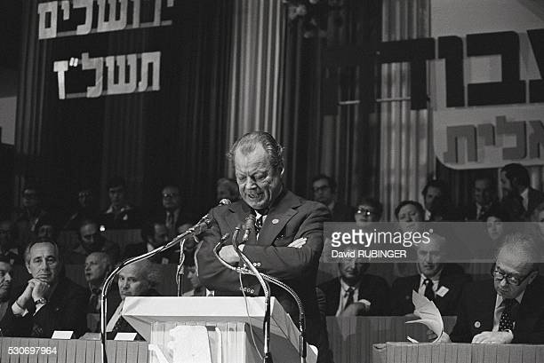 Willy Brandt speaks to a labor party convention while a campaigning Shimon Peres listens with other dignitaries circa 1973