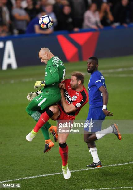 Willy Caballero of Chelsea attempts to win a header over Laurent Depoitre of Huddersfield Town during the Premier League match between Chelsea and...