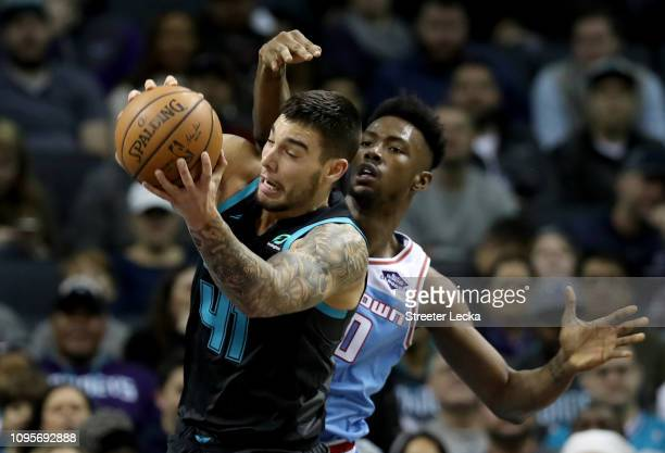Willy Hernangomez of the Charlotte Hornets battles for a loose ball against Harry Giles of the Sacramento Kings during their game at Spectrum Center...