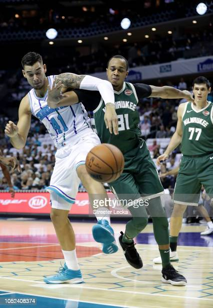 Willy Hernangomez of the Charlotte Hornets goes after a loose ball against John Henson of the Milwaukee Bucks during their game at Spectrum Center on...