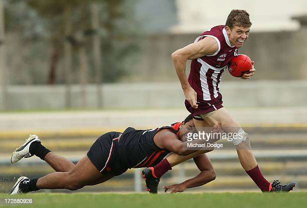 Willy Rioli Jnr of Northern Territory tackles Hayden BertoliSimmons of Queensland during the round five AFL Under 18s Championship match between...