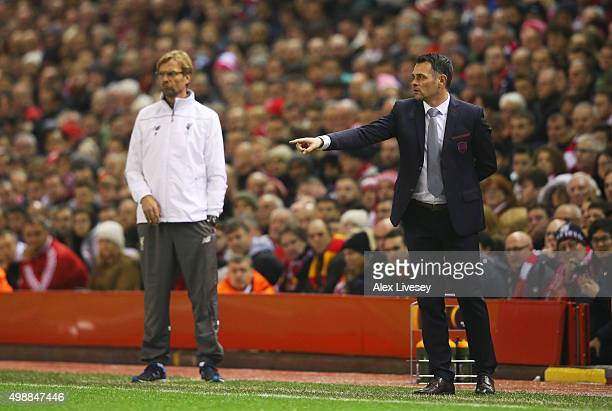 Willy Sagnol manager of Bordeaux signals as Jurgen Klopp manager of Liverpool looks on during the UEFA Europa League Group B match between Liverpool...
