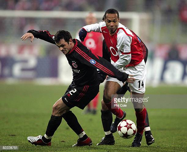 Willy Sagnol of Bayern Munich tackles Thierry Henry of Arsenal during the Champions League second round first leg match between Bayern Munich and...