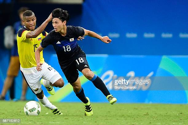 Wilmar Barrios player of Colombia competes for the ball with Takumi Minamino of Japan during 2016 Summer Olympics match between Japan and Colombia at...