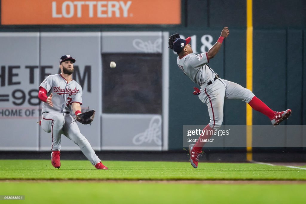 Wilmer Difo #1 of the Washington Nationals and Bryce Harper #34 try to catch a fly ball hit by Adam Jones #10 of the Baltimore Orioles (not pictured) during the ninth inning at Oriole Park at Camden Yards on May 30, 2018 in Baltimore, Maryland.