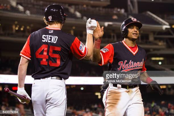 Wilmer Difo of the Washington Nationals celebrates with Andrew Stevenson after scoring a run on a bases loaded walk to Michael Taylor in the sixth...