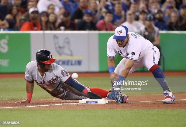 Wilmer Difo of the Washington Nationals slides safely into third base as he advances on a flyout in the ninth inning during MLB game action as...