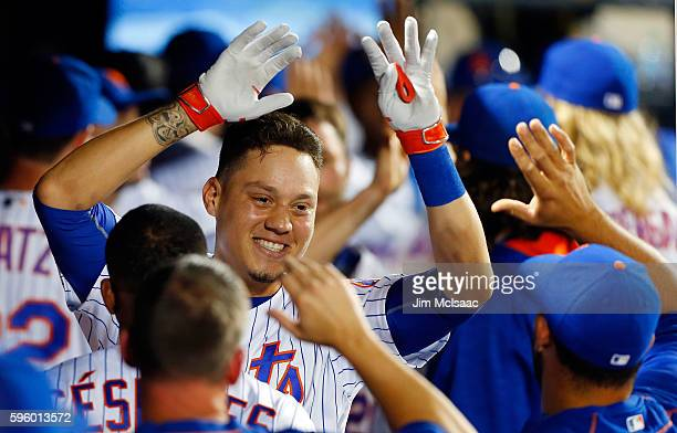 Wilmer Flores of the New York Mets celebrates his fifth inning grand slam home run against the Philadelphia Phillies with his teammates in the dugout...