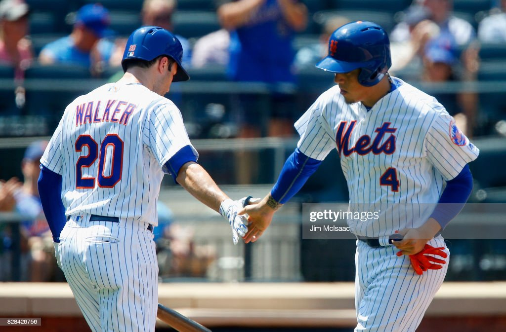Wilmer Flores #4 of the New York Mets celebrates his fifth inning home run against the Texas Rangers with teammate Neil Walker #20 at Citi Field on August 9, 2017 in the Flushing neighborhood of the Queens borough of New York City.